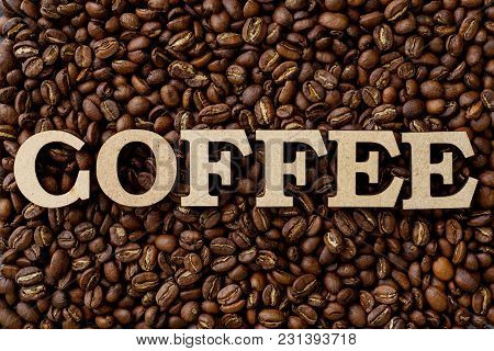 Top View Of The Word Coffee With Wooden Craftwork, Background Coffee Beans.