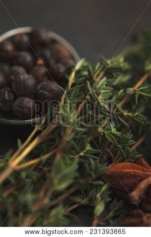 Anise Star, Some Sprigs Of Thyme And Juniper In Metal Teaspoon On Old Dark Background. Selective Foc