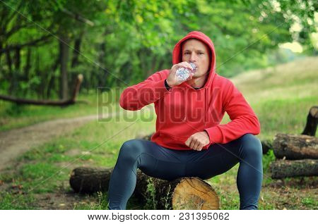 Young Athletic  Jogger In A Red  Jacket With A Hood And Black  Leggings Sits On A Log And Drink Wate