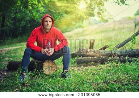 Runner In A Red Sports Jacket With A Hood And Black  Leggings Sits On A Log And Holds Bottle With Wa