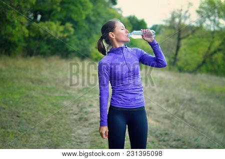Woman In A Blue Sports Jacket With A Hood And Black  Leggins Drink Water From The Bottle