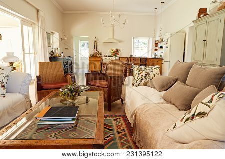 Interior Of A Comfortable Living Room In A Country Style Residential Home With The Kitchen In The Ba