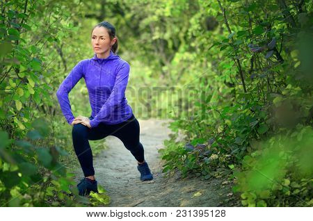 Caucasian Athletic Girl In Blue Shirt And Black Sports Leggins Performs Warming-up With Legs  Before