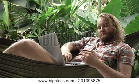 Man Banking Online With Credit Card And Laptop While Sitting On Hammock, Exotic Background