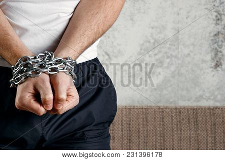 Close-up, Men's Hands Are Chain-bound. The Concept Of Arrest, Imprisonment, Cumbersome, Justice. Cop