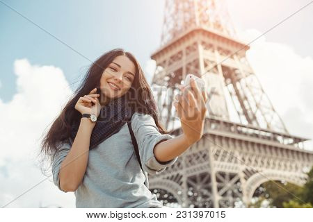 Happy Travel Woman Taking Funny Selfie With Her Mobile Phone Near The Eiffel Tower, Paris. Portrait
