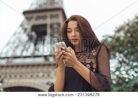 Happy Travel Woman Using Smartphone Near The Eiffel Tower And Carousel, Paris. Portrait Of Travel To