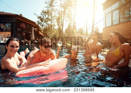 Multiethnic Company Of Friends In Swimming Pool. Company Of Young People Spend Weekend In Pool. Guys