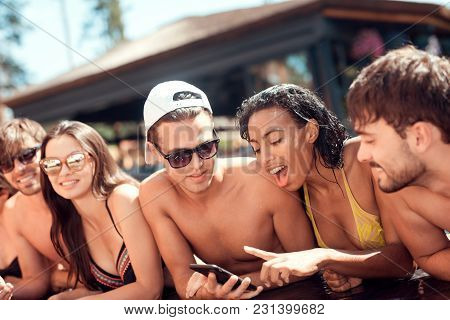 Company Of Young People Share Photos Taken On Smartphone In Pool At Summertime. Company Of Friends A