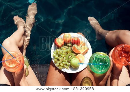 Top View. Girls In Swimsuits Eat Fruits And Drink Cocktails In Swimming Pool In Summertime. Summer V