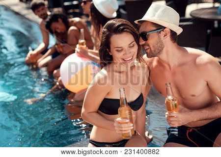 Young Guy In Summer Straw Hat Flirts With Girl In Swimsuit Sitting In Pool. Swimming Pool Party. Com