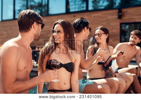 Summer Vacation Friends Together At Swimming Pool Party. Young People Spend Weekend In Pool. Holiday