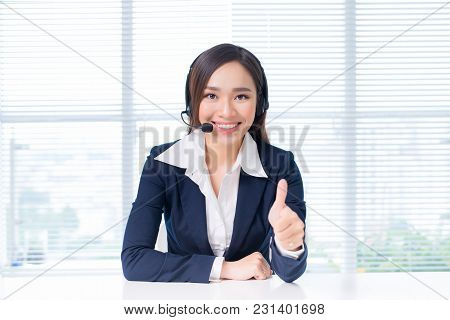 Lovely Asian Online Operator Consulting Clients Online Showing An Ok Gesture