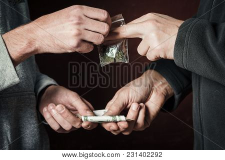 Hand of addict man with money buying dose of cocaine or heroine or another narcotic from drug dealer. Drug abuse and traffic concept. poster