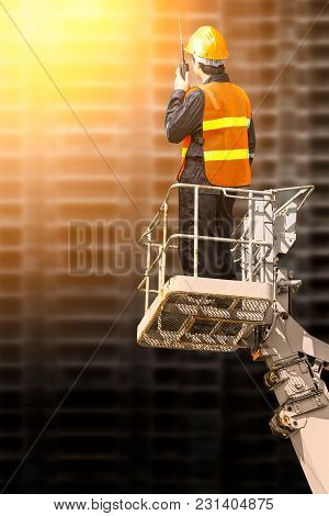 Engineer Man Using Portable Radio In Cabin Basket Crane On Construction Site Background