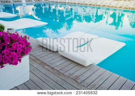 Swimming Pool With Chaise-longue In Water. Vacation And Recreation Concept. Hotel Resort Pool On Sun