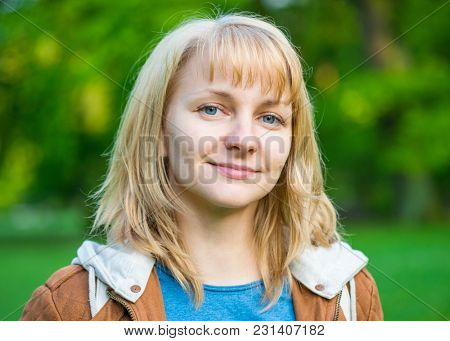 Portrait of attractive smiling caucasian young woman in spring park looking at camera - close-up outdoors.