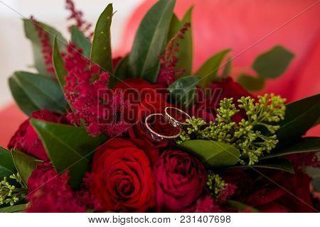 Golden Wedding Rings Lie In A Bud Of Red Rose. Wedding Rings Lie On A Flower Bud