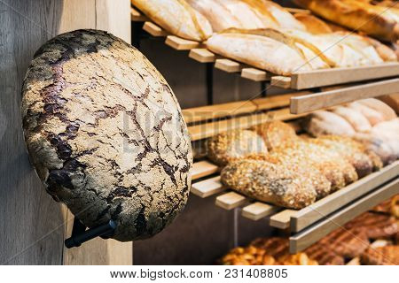 Freshly Baked Bread And Bakery Products On The Counter. Focus On A Loaf Of Bread