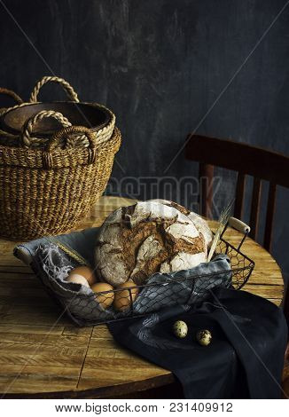 Loaf Of Rye Bread In A Basket With Chicken Eggs On The Table