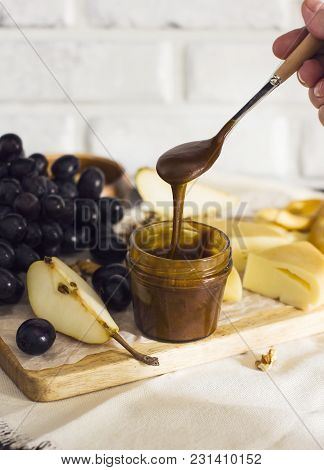 Honey Flows From Spoon Into Jar On Wooden Board With Fruit And Cheese