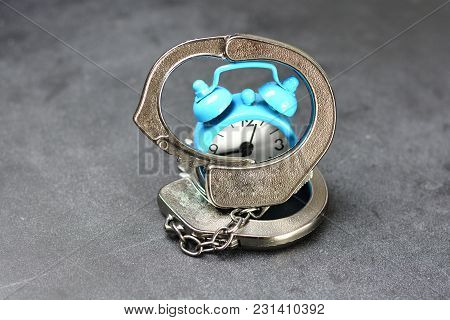 Time Slave Or Prisoner Of The Time Concept With Metallic Handcuffs And Alarm Clock On Dark Backgroun