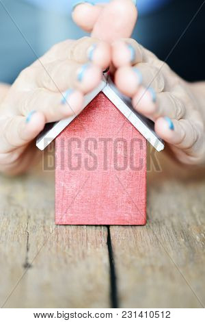 Colorful Toy House Protected By Woman Hand On Wooden Table, House Or Family Insurance Concept