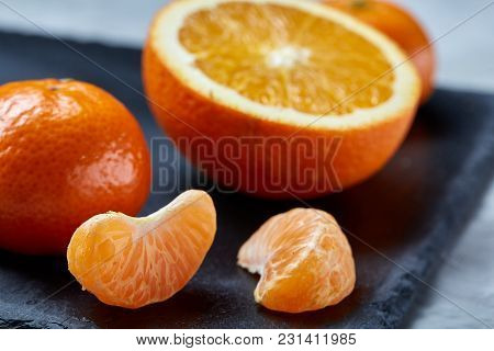 Close-up Of Whole And Half Cut Fresh Tangerine And Orange On Black Stone Cutting Board Over White Te