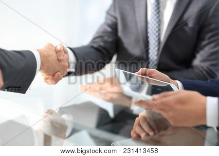 Two confident businessmen shaking hands during a meeting in the