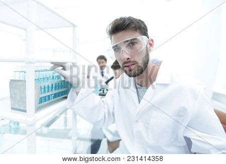 Young male scientist looking at a sample in a test tube side vie