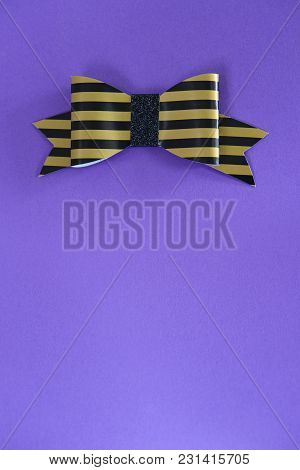 Black And Golden Striped Bow Tie Over Ultra Violet Background. Copy Space. Free Space For Text