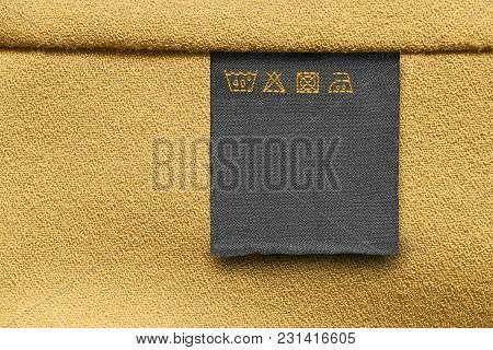 Care Clothes Label On Yellow Textile Background Closeup