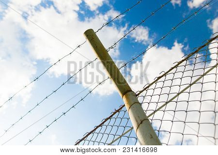 Fence With Barbed Wire Against The Blue Sky .