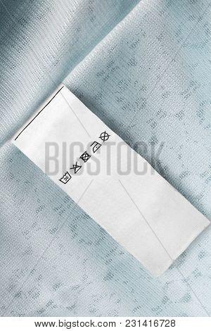 Care Clothes Label On Pastel Blue Textile Background Closeup