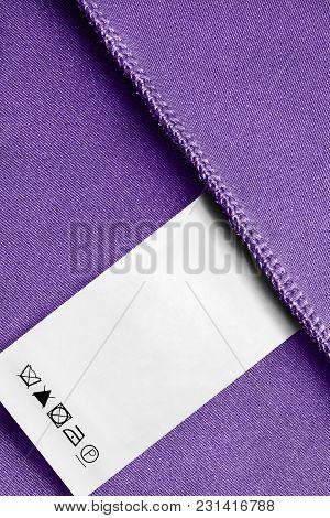 Care Clothes Label On Purple Textile Background Closeup