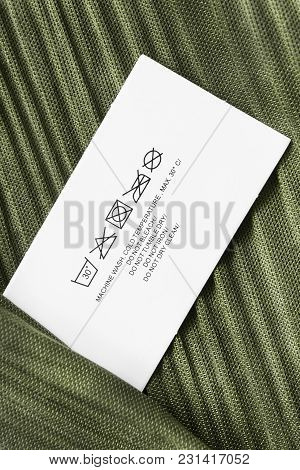 Care Clothes Label On Green Satin Background Closeup