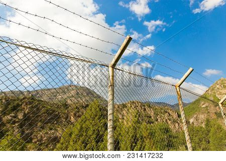 Fence With Barbed Wire In The Open Air .