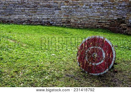 A Wooden Target For A Crossbow With A Red Color With White Circles In The Courtyard Of An Ancient Ca