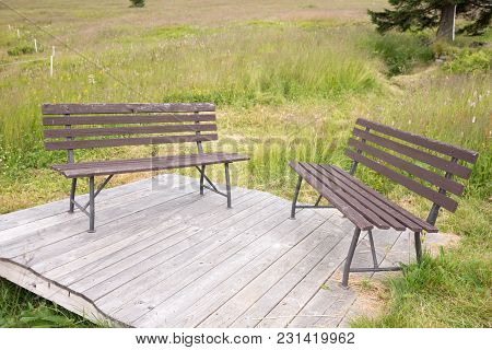 Two Wooden Benches On A Wooden Platform In The Park