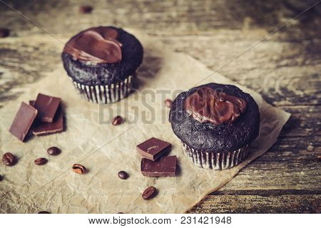 Chocolate Cupcakes With Icing On Wooden Background.