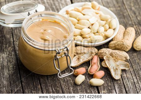 Peanut butter in jar and peanuts on wooden table.