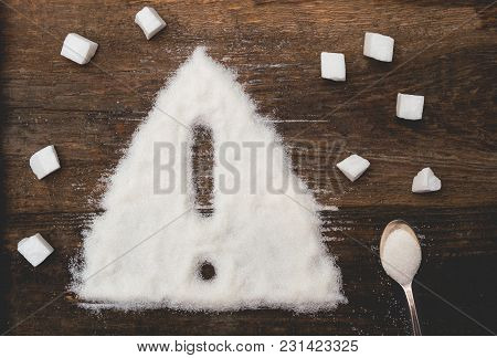 Sign Of Warning Attention Made Of Granulated Sugar. A Conceptual Photo Illustrating The Harm From Co