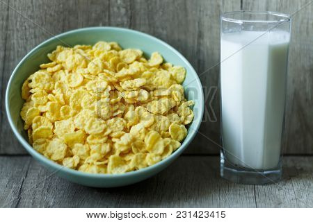 Corn Flakes Are Poured Into A Green Plate, And Next Is A Glass Of Milk, Breakfast