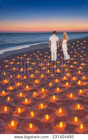 Loving Couple In White Cloth At Tropical Sunset Ocean Sandy Beach Decorated With Lot Of Candles Ligh