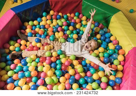 High Angle View Of Happy Little Boy Lying In Pool With Colorful Balls
