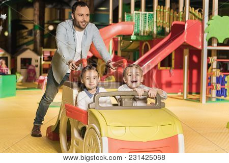 Smiling Father Carrying Adorable Happy Kids On Toy Car At Entertainment Center