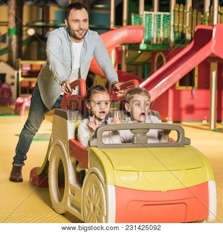 Happy Father Carrying Kids On Toy Car At Entertainment Center
