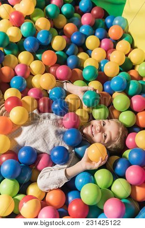 High Angle View Of Cute Little Boy Smiling At Camera While Lying In Pool With Colorful Balls