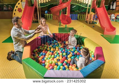 High Angle View Of Happy Family With Two Adorable Kids Playing With Colorful Balls In Entertainment