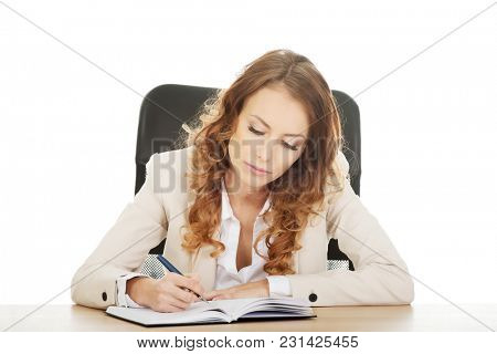 Focused businesswoman writing note by a desk.